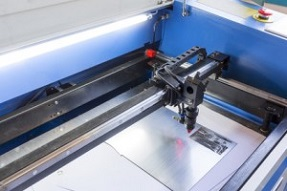 Laser machine is cutting an image on a flat sheet ot steel in a university laboratory.