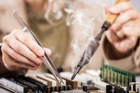 Manual worker human hand holding soldering iron tool repairing computer electronics circuit board