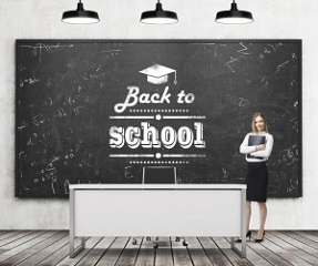A beautiful girl with black document folder and teacher's desk in a modern school. A black chalkboard on the wall with written down phrase - Back to school. Three black ceiling lights.